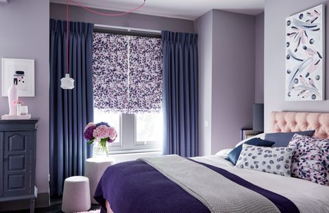 Bedroom with blue pinch pleat curtain paired with a floral roman blind
