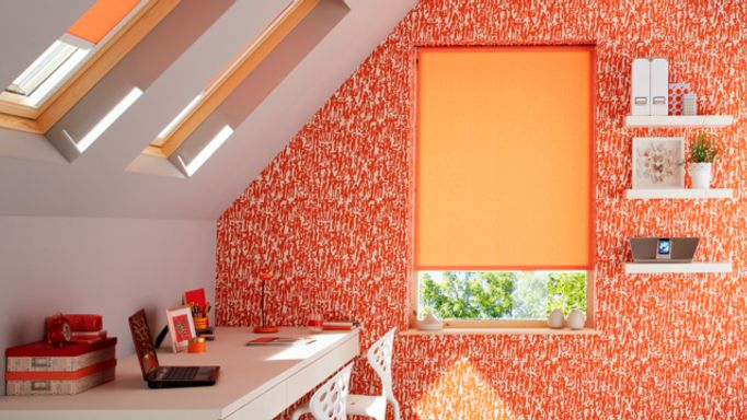 An attic room with orange walls and a large window fitted with a Roller blind in Sherbourne Orange fabric