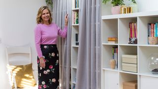 Liz Earle stood in front of a bookshelf with voile curtains fitted to it