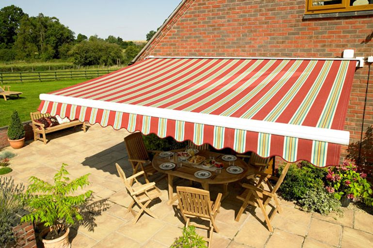 A red striped awning hanging over patio furniture