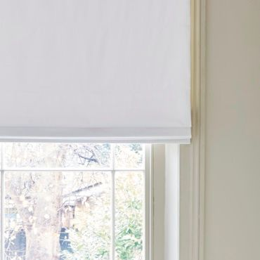 white roman blinds with a view of a garden from a window