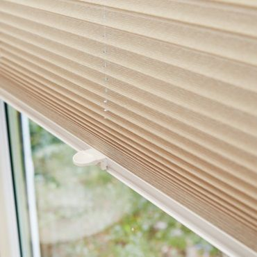 cream pleated blinds in a window close up