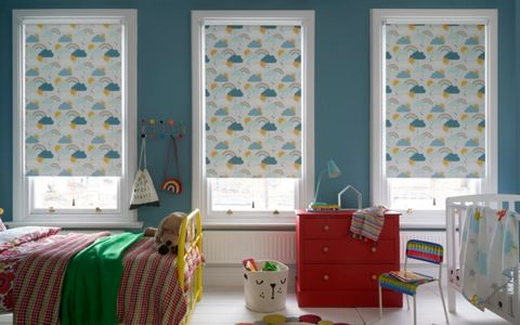 A child's bedroom with 3 windows, each fitted with a Roller blind in Rainbow Dreams fabric