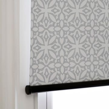 Roller blind in Marrakesh Stone fabric which is white and gray with a geometric pattern