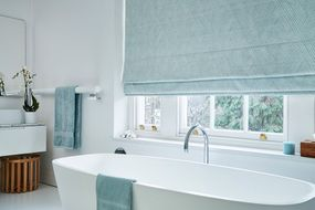 Bathroom with large ceramic white tub and sash windows dressed with pastel blue roman blinds