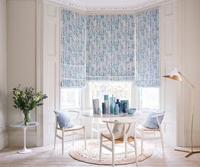 Traditional dining area in a bay window enclave dressed with blue floral roman blinds