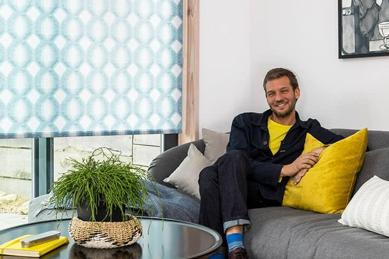 Charlie Luxton sat on a gray couch with yellow cushions in front of a window fitted with a blind in Brindle Denim Drift