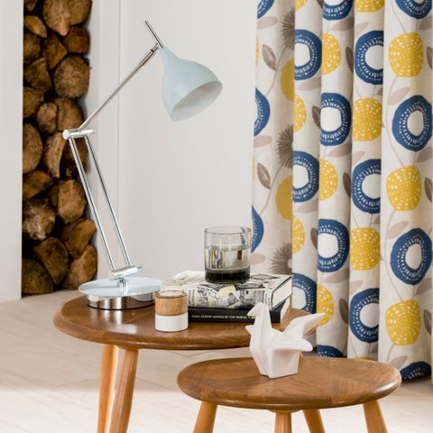 A set of tables with a white angle poise lamp with blue and yellow patterned curtains in the background