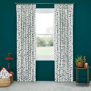 Abigail Ahern Wolfe Smoulder Curtains set against dark teal walls in living room with side table