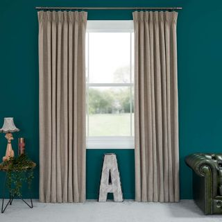 Abigail Ahern Amis Buff Curtains set against dark teal walls in living room