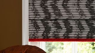 Sofa next to window covered by Cadillac Noir Roman blinds with Colette Vixen fringing