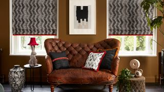 Abigail Ahern living room with Cadillac Noir roman blinds with colette vixen fringing and cley mole and wolfe smoulder cushion product box
