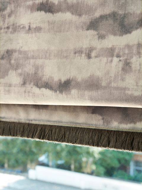 A closeup of a Jago Tabac Roman blind fringed with Colette Minx