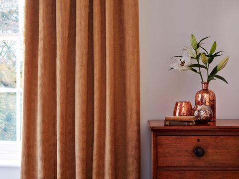 Roche Ochre curtains hanging in a cosy traditional bedroom