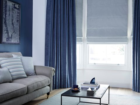 Fascination Denim curtains hanging in front of Allure Silver Roman blinds in a modern living room