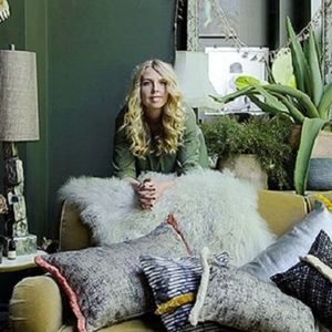 Abigail Ahern leaning over a sofa covered