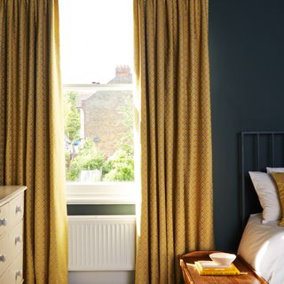 A bedroom with a sash window fitted with Curtains in Eclipse Mimosa fabric