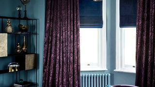 Radiance Midnight Roman blinds with Broadleigh Aubergine curtains hung in an opulent living room