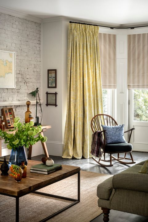 Howard Natural Roman blinds with Oralia Ochre curtains hung in living room