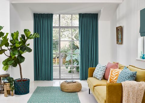 Clarence Teal curtains hung in a comfy living room with plants around