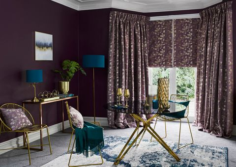 Stylish Lavender curtains and Roman blinds hung in the window of a luxurious living room