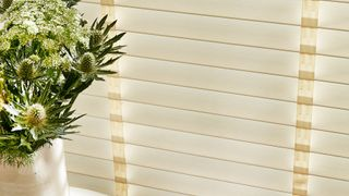 Close up of ivory wooden shutters with tape next to a side table with a vase of flowers