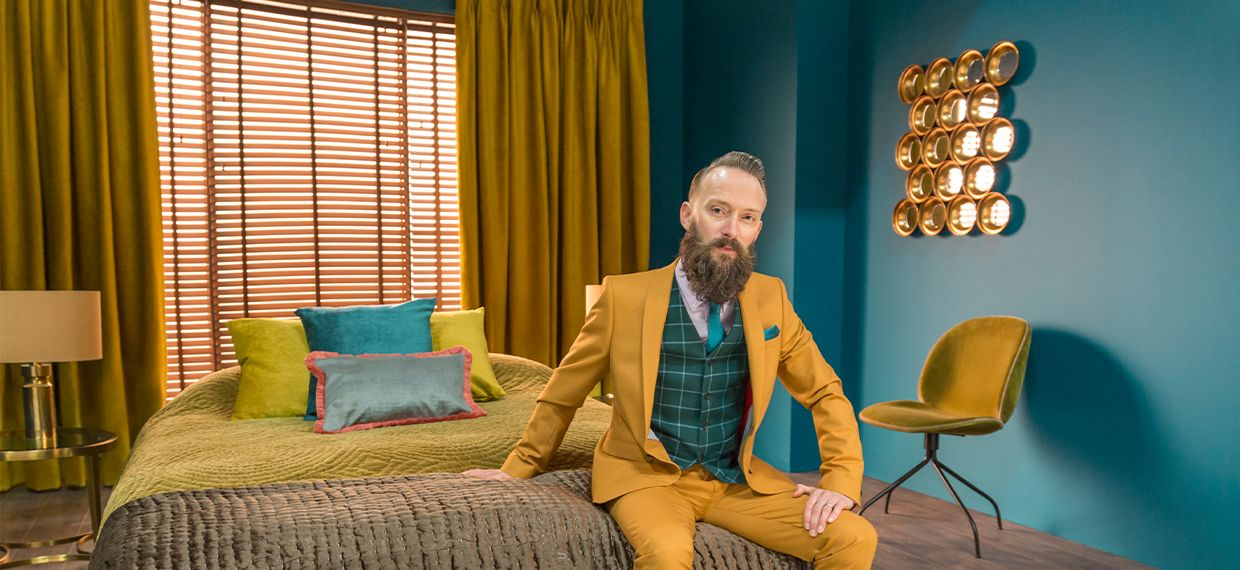Man in mustard suit sitting on bed from Hillarys advert