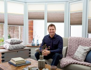 George Clarke sitting in a conservatory fitted with Thermashade TM blinds