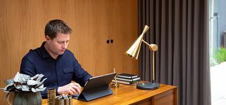 George Clarke in home office with Tetbury Charcoal curtains