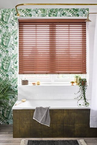 Nutmeg Faux Wood Blinds in bathroom window above a bath with tropical print wallpaper