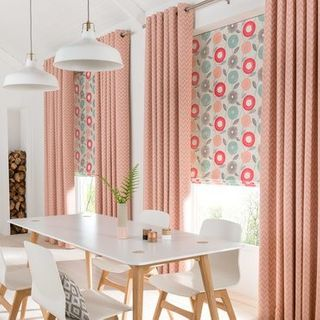 Horizon Salmon Curtains paired with patterned roman blind in a dining room with white furniture