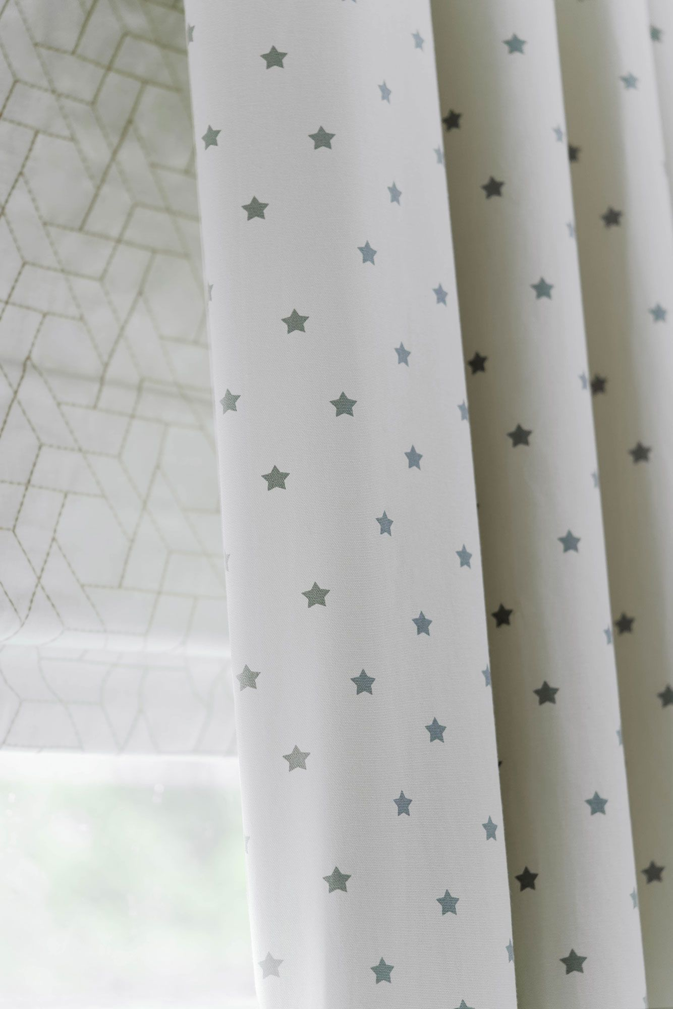 Close up of Polaris Ivory curtains and Jive Mallow romans in children bedroom