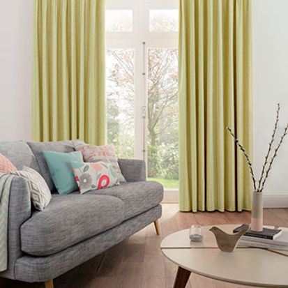 Furnished living room with Lotta Citron curtains over a glass door