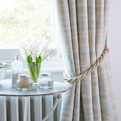 Tied back Riviera Mist curtains by a stone coffee table