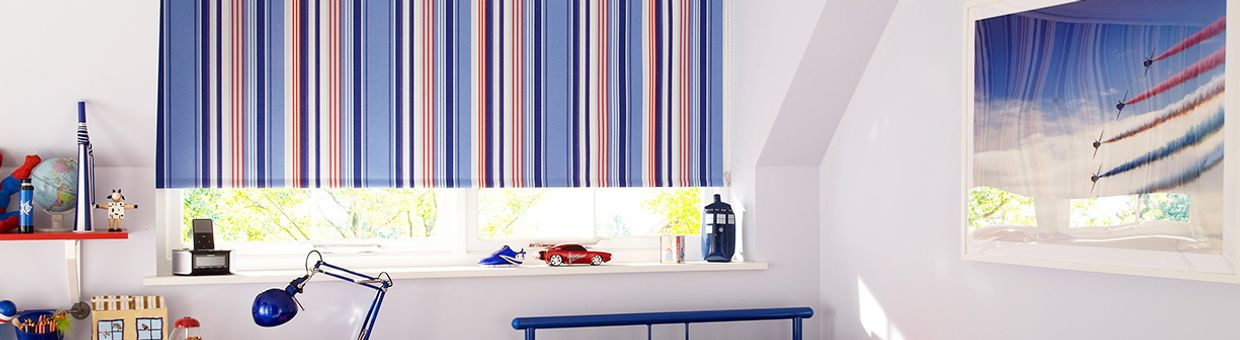 Child's bedroom with a striped blackout roller blind in Circus Royal fabric in the window.