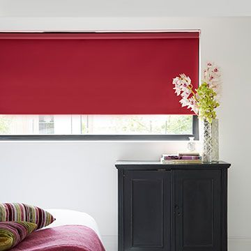 Plain red Cordova Raspberry roller blind hung in bedroom