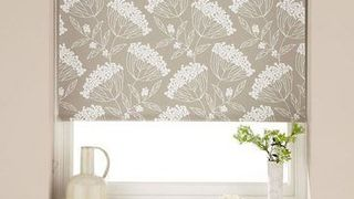 Patterned Elsham Natural roller blinds hung in bedroom