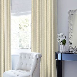 Anouk Straw Curtains in a dressing room behind a white fabric chair