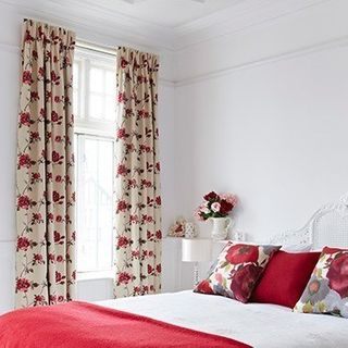 Lambay Rose Curtains in bedroom with bed made with red accent furnishings