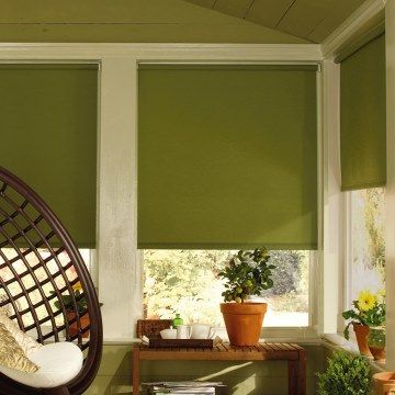 Plain dark green Acacia Olive roller blind hung in conservatory