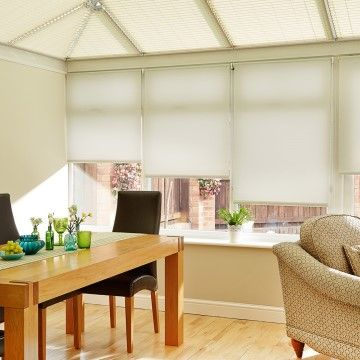 Plain white Cordova White roller blinds hung in conservatory