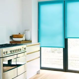 Plain blue Ravenna Aqua roller blind hung in kitchen