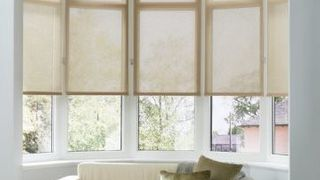 Plain light Tatum Beige roller blinds hung in living room