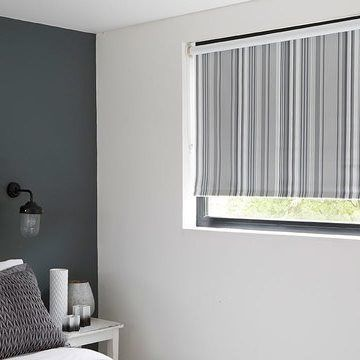 Roller blinds in Lester Silver hung in stylish grey bedroom