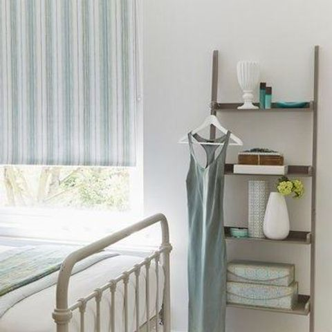 Roller blinds in striped Melia Mineral, hung in a stylish urban bedroom