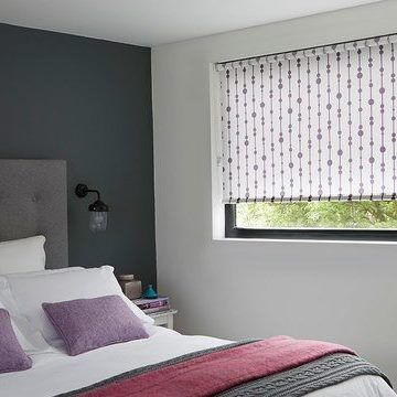Retta Aubergine roller blind hung in bedroom