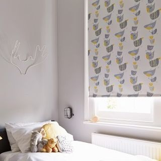 Bird patterned Dickie Birds Grey roller blind hung in child's bedroom
