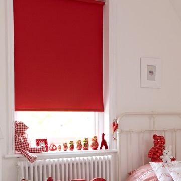 Plain red Cordova Red roller blind hung in child's bedroom