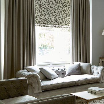 Living room with furniture and one large window with Aurella Ash roman blinds and Harlow Charcoal curtains