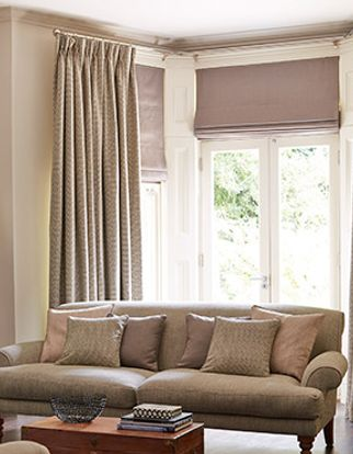Abacus Liqourice Curtains layered with roman blinds in a bay window in a living room with neutral furniture